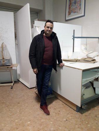 Joaquín Rubio junto a una mesa de trabajo de su taller.